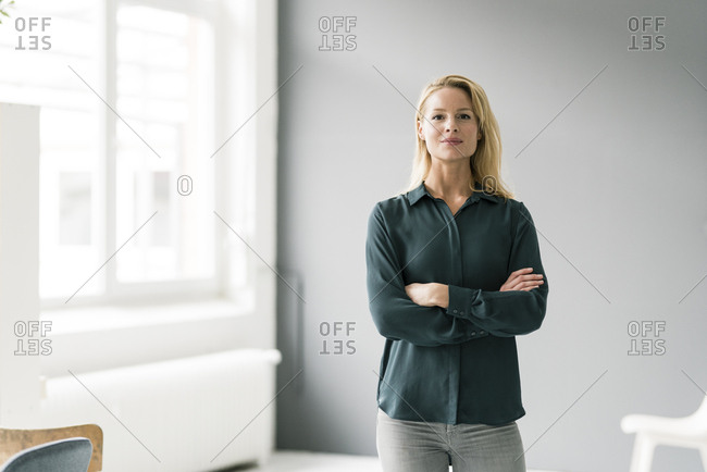 Successful- blond businesswoman standing in bright room- with arms crossed