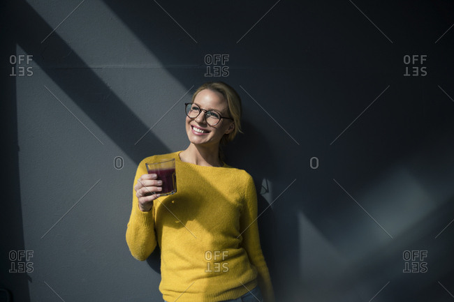 Woman in yellow pullover- holding glass of tea- enjoying the sun