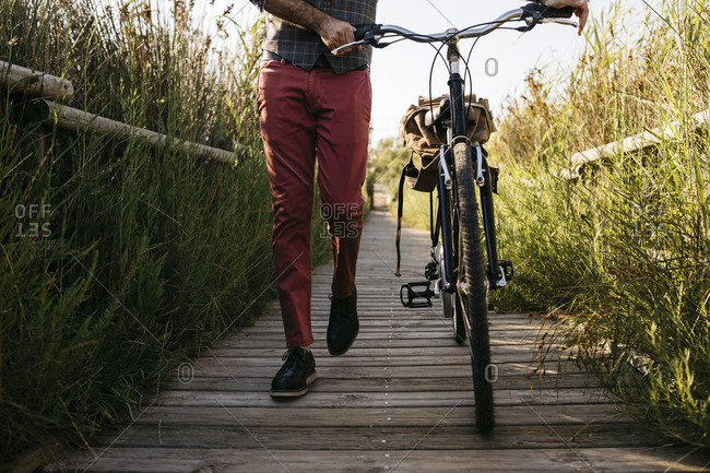 Well dressed man walking with his bike on a wooden walkway in the countryside after work