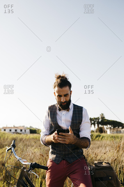 Well dressed man with his bike in the countryside using cell phone