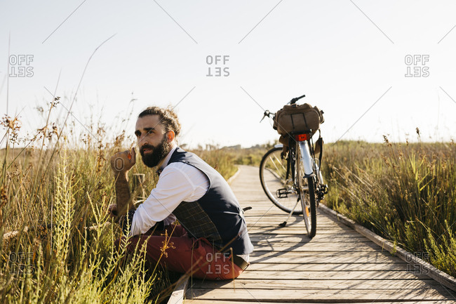 Well dressed man sitting on a wooden walkway in the countryside next to a bike