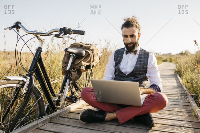 Well dressed man sitting on a wooden walkway in the countryside next to a bike using laptop