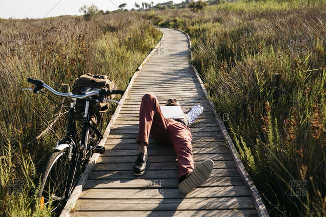 Well dressed man with laptop lying on a wooden walkway in the countryside next to a bike