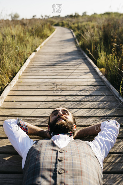 Well dressed man lying on a wooden walkway in the countryside