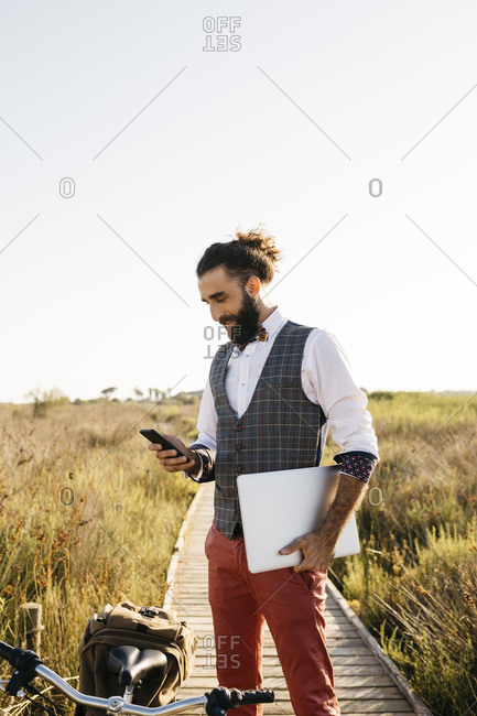 Well dressed man standing on a wooden walkway in the countryside next to a bike using cell phone