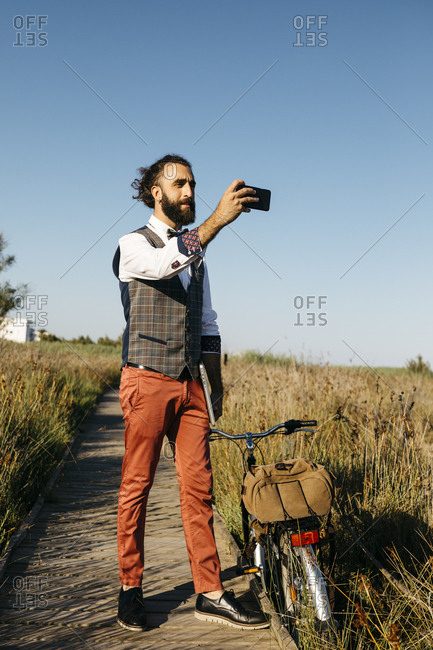 Well dressed man with his bike on a wooden walkway in the countryside taking a cell phone picture