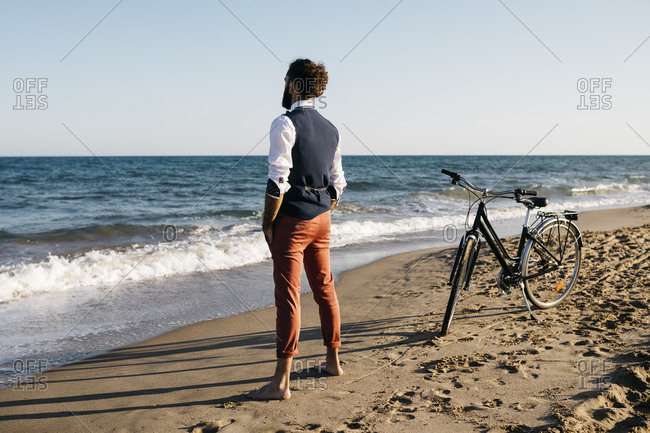 Well dressed man with his bike standing on a beach