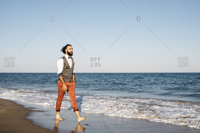 Well dressed man walking on a beach at water's edge