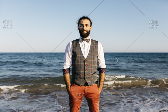 Portrait of a well dressed man standing on a beach at water's edge