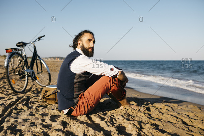 Well dressed man with his bike sitting on a beach