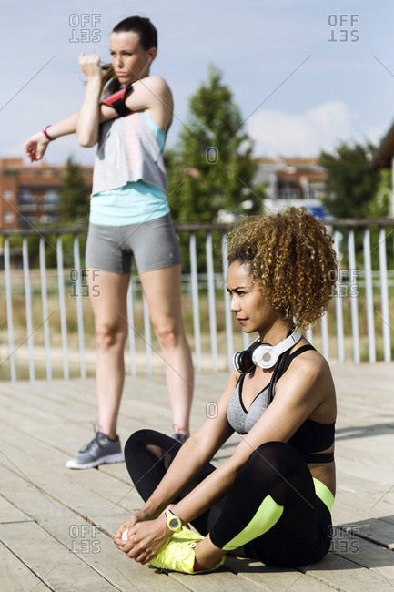 Two sporty young women doing stretching exercise