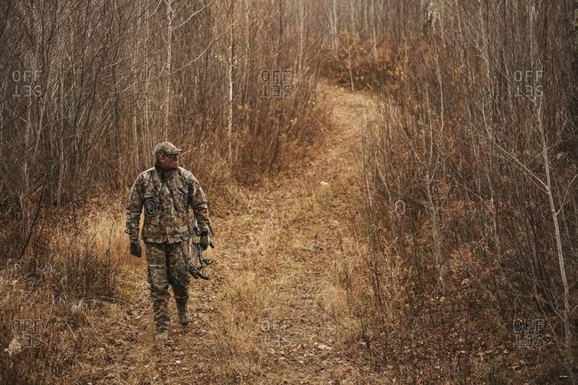 Bowhunter ground stalking turkey while walking on old logging trail