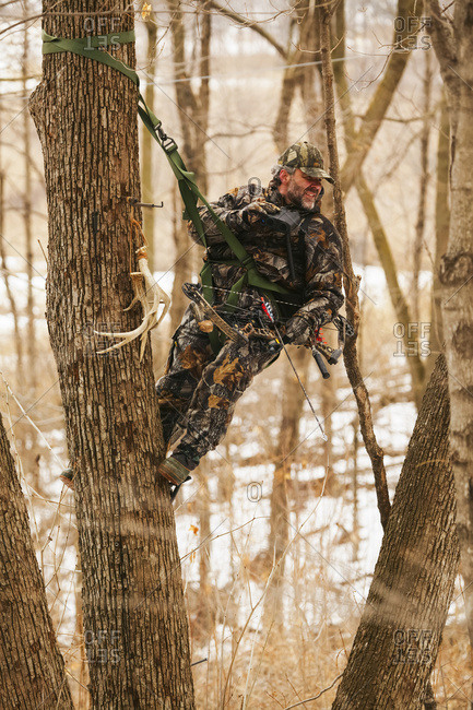 Hunter In Tree Saddle Tree Stand In Winter During A Deer Hunt