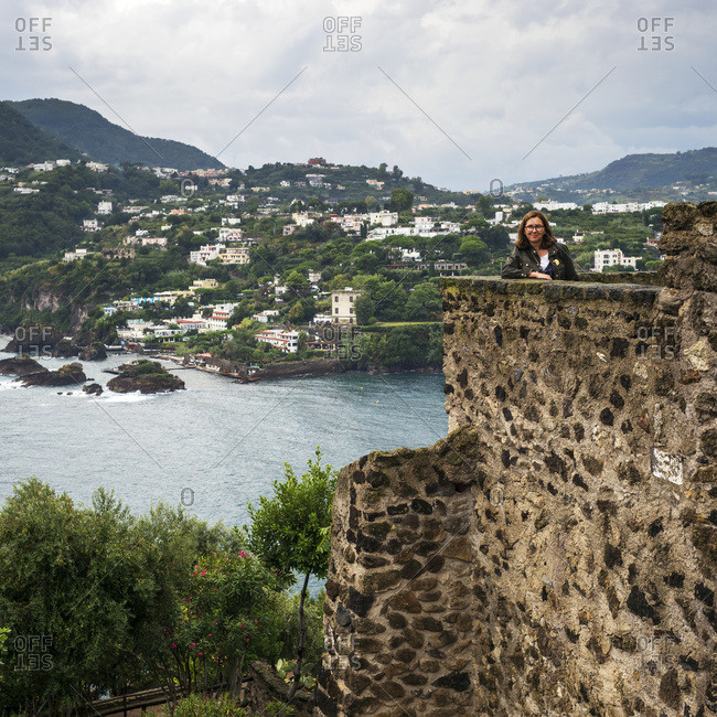 A woman stands posing from an old stone wall of Aragonese Castle in Campania, Italy