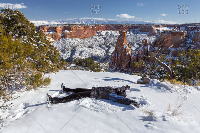A woman makes a snow angel in the snow in front of the Colorado National Monument