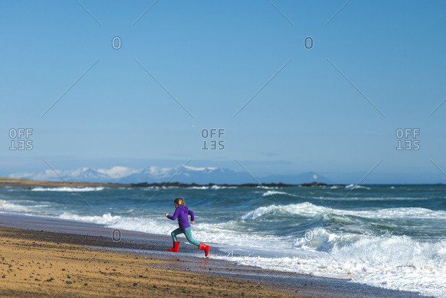 Girl running from waves on Langaholt beach, Iceland