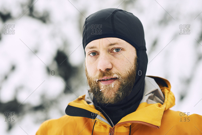 Portrait of a man with a frosty beard wearing a head covering against a snowy background in British Columbia, Canada