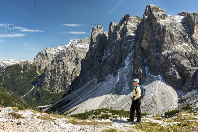 Female hiker overlooking valley against rugged mountain range and blue sky in Sesto, Bolzano, Italy