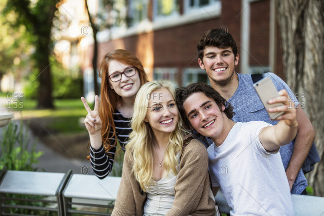A group of four friends sitting on a bench taking a selfie on a university campus in Edmonton, Alberta, Canada