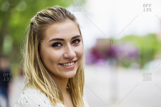 Portrait of a beautiful young woman on a university campus with the background blown out