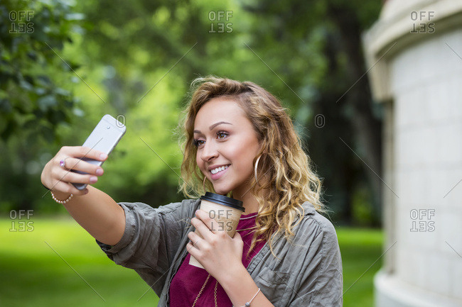 A beautiful female university student taking a selfie on campus