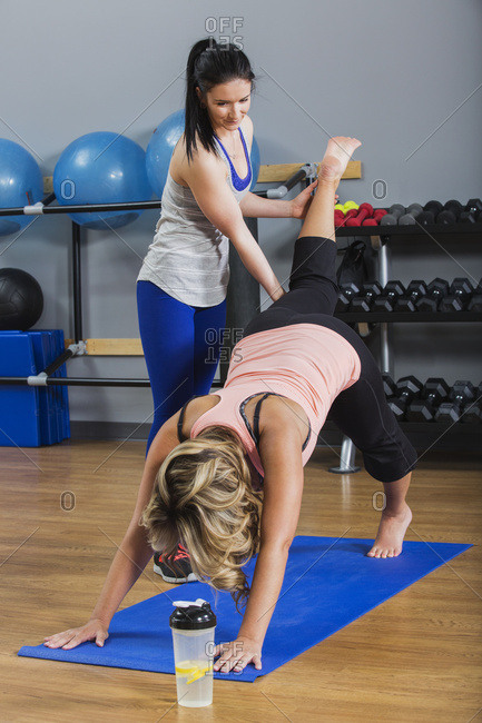 A middle-aged women doing a downward dog leg lift yoga exercise at the gym with her personal trainer