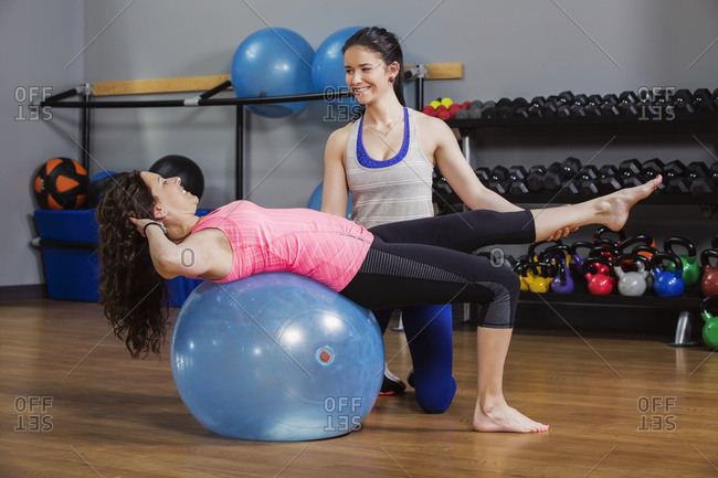 An attractive middle-aged woman working out using a balance ball with her trainer
