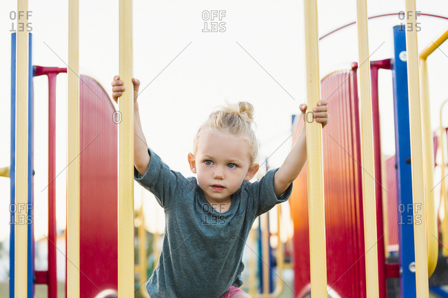 A young girl with blond hair playing in a playground and climbing up a rock ladder on a warm fall day