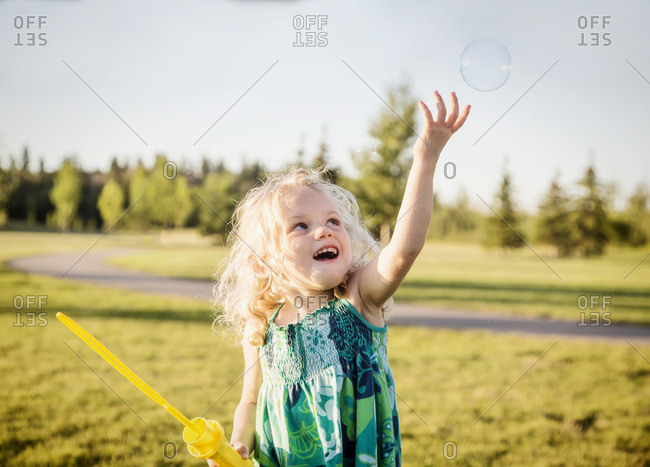 A cute young girl with blond hair blowing a bubble and trying to catch it in a park on a warm fall day