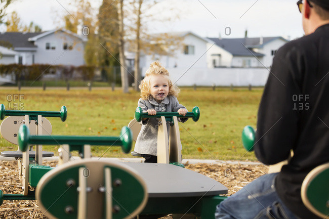 A cute young girl playing on a seesaw with her dad in a playground during the fall