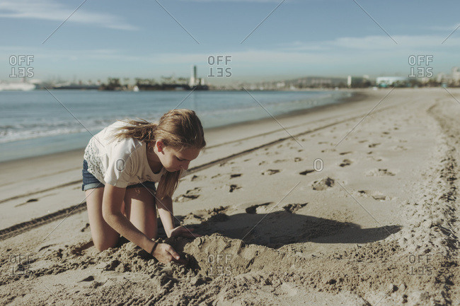 A girl playing in the sand at the beach in Long Beach, California