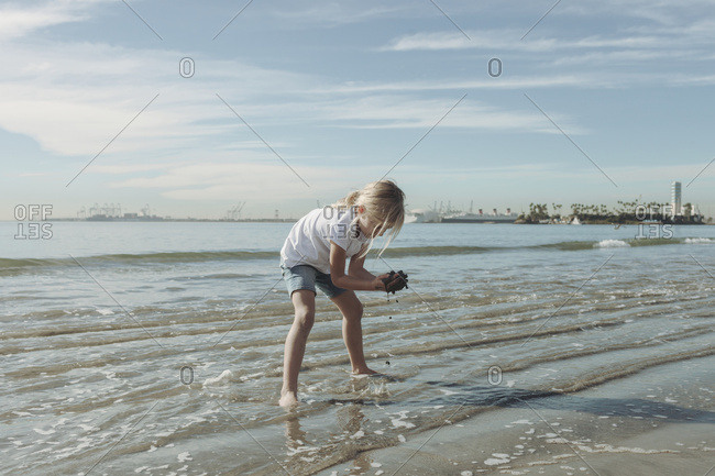 A young girl plays in the wet sand along the shoreline in Long Beach, California
