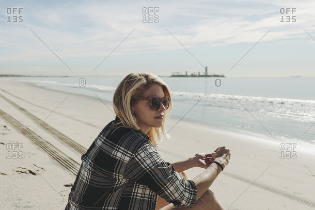 A woman sits on a beach looking out to the water in Long Beach, California