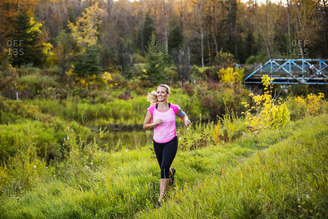 An attractive middle-aged woman runs along a creek in a city park at sunset