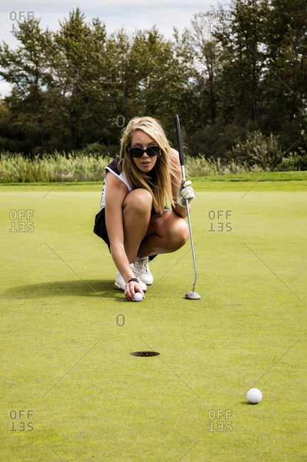 An attractive female golfer lines up her shot before making a short putt
