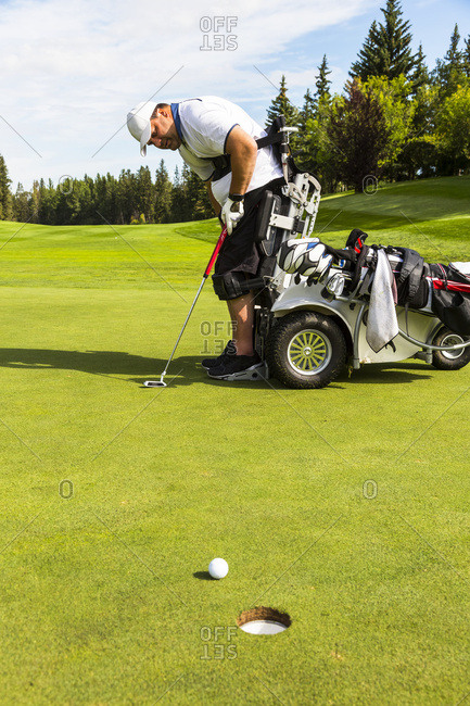 A physically disabled golfer chipping a ball using a specialized golf assistance motorized hydraulic wheelchair