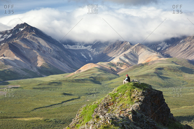 Senior Man Sits On A Rock Outcrop At Polychrome Pass With Alaska Range In The Background