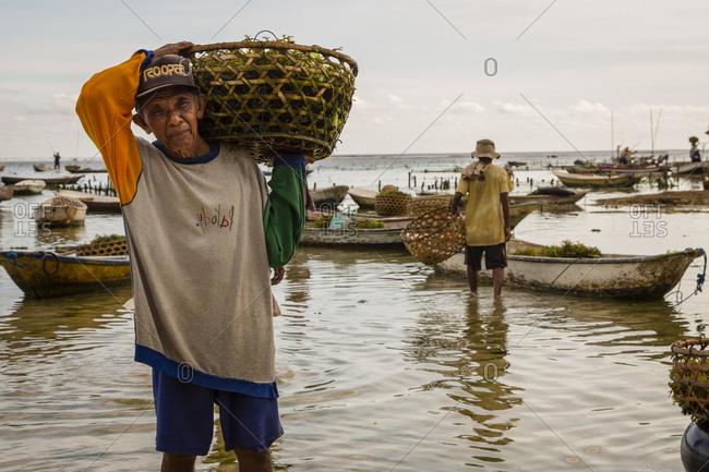 Indonesia, Bali, Nusapenida - April 27, 2014: Old man carrying basket of seaweed