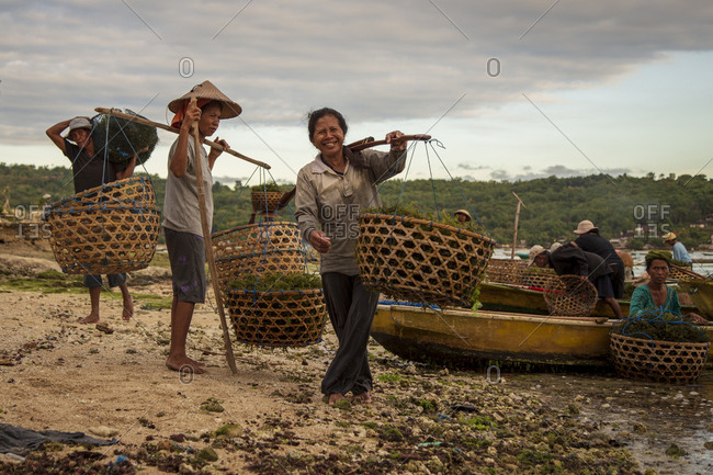 Indonesia, Bali, Nusapenida - April 27, 2014: Two women and one man carrying baskets filled with seaweed
