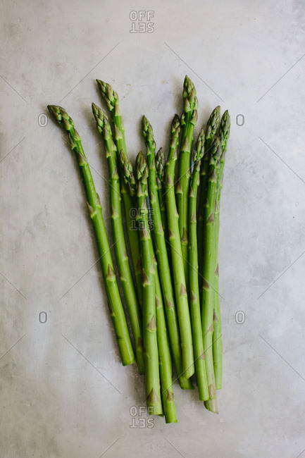 A bunch of asparagus spears rest on a gray rustic background