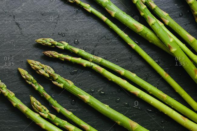 Fresh picked asparagus spears on black slate countertop