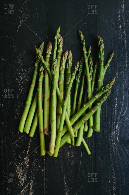 Bunch of fresh cut garden asparagus on a dark rustic wooden table