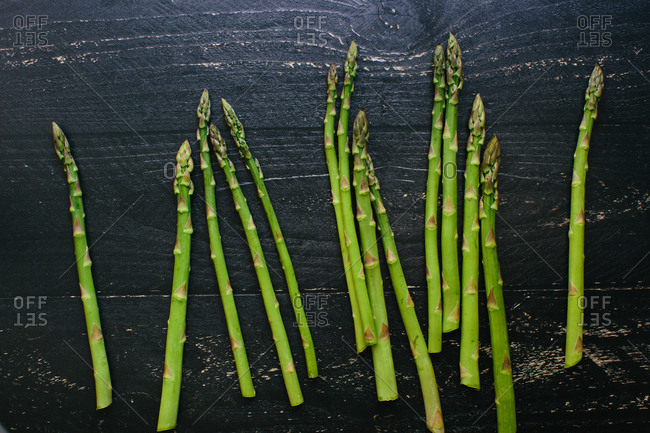 Fresh cut asparagus spears lay on a black painted rustic wooden table