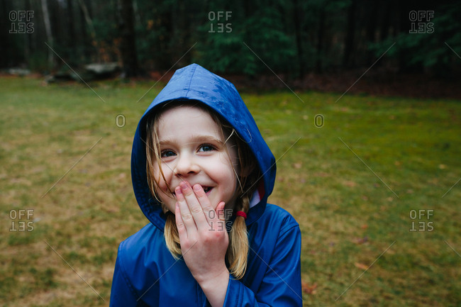 Young girl in a blue raincoat giggling in the rain