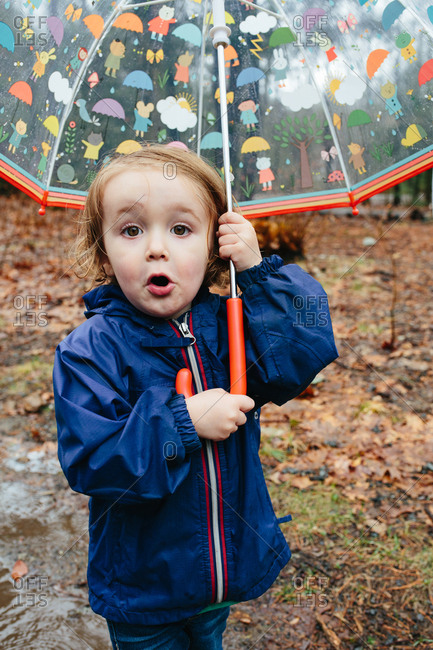 Toddler child holding umbrella in the rain and looking surprised