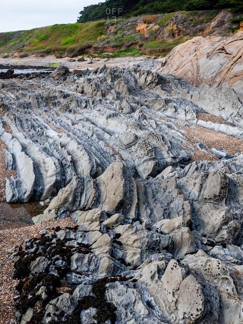 Layers of weathered stone on coastal beach