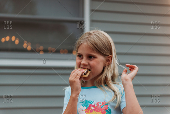 Young girl taking a bite of a s'more
