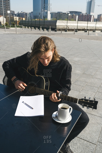 man playing the guitar and studying music