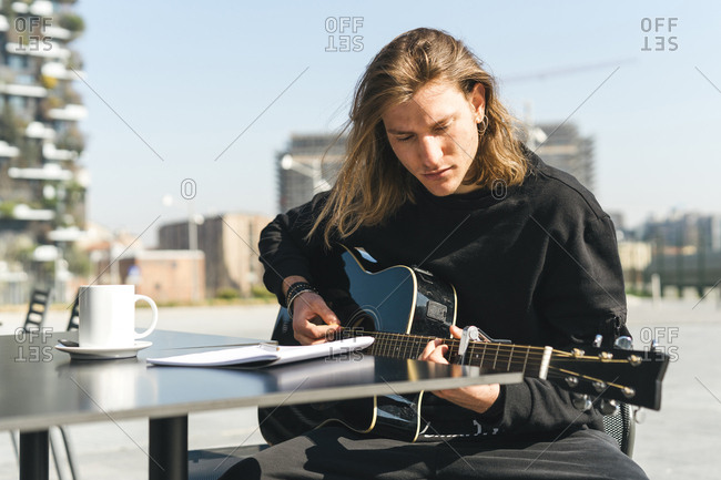 man playing the guitar and studying music composition