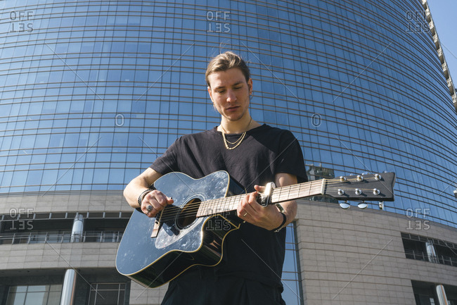 white man stand in front of a sky scraper is playing a classic guitar